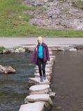 Korsning för ung kvinna som kliver stensovedale Royaltyfri Fotografi