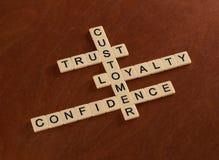 Korsordpusslet med ord litar på, lojalitet, förtroende kund royaltyfria bilder