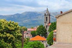 Korsykanina krajobraz, starzy domy i dzwonkowy wierza, Zdjęcia Stock