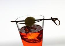 Kort drankglas met rode vloeistof, olijf, ijsblokjes Royalty-vrije Stock Foto
