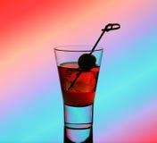 Kort drinkexponeringsglas med röd flytande och grön oliv Royaltyfria Bilder