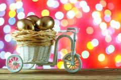 kort easter Guld- ägg i en cykelvagn Ägg lyckliga easter Arkivfoto