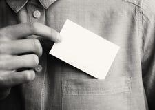 Kort för affär för manvisning tomt Den vuxna affärsmannen tar ut det tomma kortet från facket av hans skjorta Ordna till för ditt arkivbilder