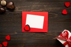Kort för dag för valentin` s på träbakgrunden Gåvaask, röda hjärtor och choklad på träskrivbordet Arkivbild