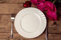 Kort för hälsning för dag för St-valentin` s med plattan, kniven, gaffeln, gåvan och rosor Royaltyfri Foto