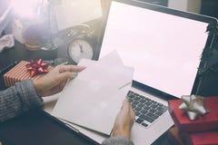 Kort för jul för hand för affärskvinna hållande och gåvaask på skrivbordet Royaltyfria Foton