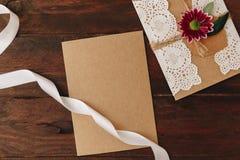Kort för lekmanna- eco för lägenhet pappers- på träbakgrund Bröllopinbjudankort eller förälskelsebokstav arkivfoton
