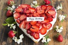 Kort för lycklig födelsedag med hjärtaostkaka med jordgubbar Fotografering för Bildbyråer