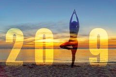 Kort 2019 för lyckligt nytt år för yoga Anseende för yoga för konturlivsstilkvinna övande som delen av numret 2019 nära stranden  royaltyfri fotografi