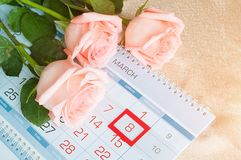 8 kort för mars - rosor över kalendern med det inramade 8 datumet för mars Arkivbild