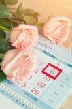 8 kort för mars - rosor över kalendern med det inramade 8 datumet för mars Arkivfoto