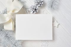 Kort för modelljulhälsning med det vita trädet och kotte som är flatlay på en vit träbakgrund, med stället för din text arkivfoton