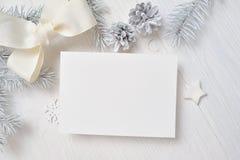 Kort för modelljulhälsning med det vita trädet och kotte som är flatlay på en vit träbakgrund, med stället för din text arkivbild