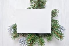 Kort för modelljulhälsning med trädet och kotte som är flatlay på en vit träbakgrund, med stället för din text arkivbilder