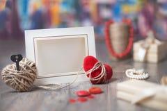 Kort för ram eller för hälsning för valentindagfoto och handgjorda hjärtor över trätabellen Royaltyfria Bilder