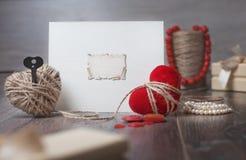 Kort för ram eller för hälsning för valentindagfoto och handgjorda hjärtor över trätabellen Royaltyfri Bild