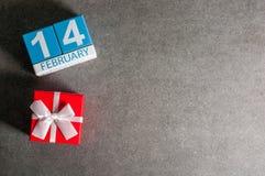 Kort för valentindaghälsning 14 Röd gåvaask med den vita pilbågen för för älsklingen 14th februari kalender på mörker Royaltyfri Fotografi