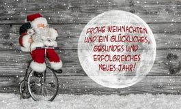 Kort för glad jul i rött och vitt med tysk text och en san Arkivfoton