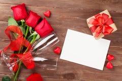 Kort för valentindaghälsning, gåvaask och röda rosor Arkivbild