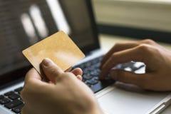 Kort i hand och skrivande in säkerhetskod genom att använda bärbar datortangentbordet Fotografering för Bildbyråer
