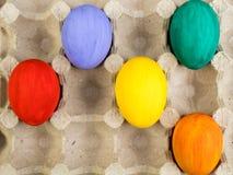 kort lyckliga easter Färgrika easter ägg på lådabakgrund Kopiera utrymme för text Arkivfoto