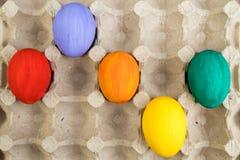 kort lyckliga easter Färgrika easter ägg på lådabakgrund Kopiera utrymme för text Royaltyfri Bild