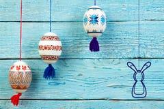 kort lyckliga easter Färgrika skinande easter ägg och kanin på blå trätabellbakgrund Kopiera utrymme för text Royaltyfria Foton