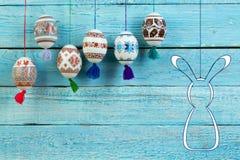 kort lyckliga easter Färgrika skinande easter ägg och kanin på blå trätabellbakgrund Kopiera utrymme för text Arkivfoto