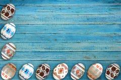 kort lyckliga easter Färgrika skinande easter ägg på blå trätabellbakgrund Kopiera utrymme för text Royaltyfri Foto