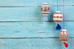 kort lyckliga easter Färgrika skinande easter ägg på blå trätabellbakgrund Kopiera utrymme för text Royaltyfri Bild