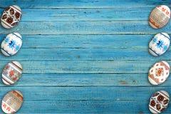 kort lyckliga easter Färgrika skinande easter ägg på blå trätabellbakgrund Kopiera utrymme för text Arkivfoto