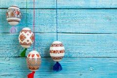kort lyckliga easter Färgrika skinande easter ägg på blå trätabellbakgrund Kopiera utrymme för text Arkivbild