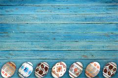 kort lyckliga easter Färgrika skinande easter ägg på blå trätabellbakgrund Kopiera utrymme för text Fotografering för Bildbyråer