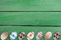 kort lyckliga easter Färgrika skinande easter ägg på grön trätabellbakgrund Kopiera utrymme för text Royaltyfria Foton