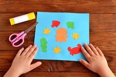 Kort med den ljusa pappers- havsdjur och fisken, lim, sax på en brun träbakgrund arkivbilder