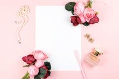 Kort med den röd och rosa färgblommaramen för penna, för smycken, för doft, på pastellfärgad bakgrund Hälsning för kvinnors eller fotografering för bildbyråer