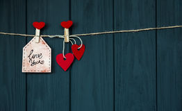 Kort med ` för kortet för ` s för lustförälskelsevalentin älskar dig naturlig kabel för ` och rött ben som hänger på lantlig svar royaltyfria bilder