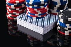 Kort och chiper för att spela poker reflekteras på en svart bakgrund Arkivbilder