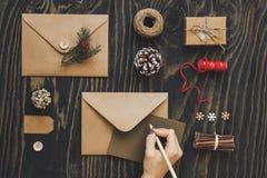 Kort och gåvor för jul handgjorda Räcka danandejulkortet på trätabellen, bästa sikt royaltyfri foto