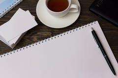 Kort, te, anteckningsbok och penna arkivbild
