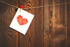Kort till dagen av St-valentin och röd hjärta på trä Royaltyfri Foto
