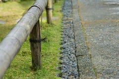 Korta bambustaket och stenar längs banan Royaltyfria Foton