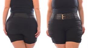 Korta flåsanden för XXL-kvinnasvart med det svarta bältet på plus formatmodellen som isoleras på vit Royaltyfri Bild