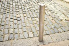 Korte metaalpool op een steenbestrating Stock Foto