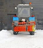 Korte onderbreking in het werk bij sneeuw het schoonmaken Sneeuwploeg dichtbij muur stock foto's