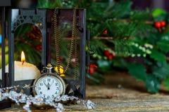 Kortet för nytt år s med julgrangran förgrena sig, den midnatta klockan, den brännande stearinljuset, guld- bollar, girlandljus p royaltyfri bild