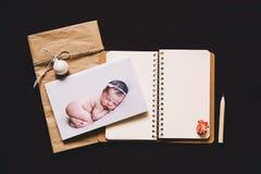 Kortet med att sova som är nyfött, behandla som ett barn och den tomma notepaden Fotografering för Bildbyråer