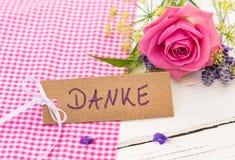 Kortet med det tyska ordet, Danke hjälpmedel tackar dig med den härliga gruppen av blommor Royaltyfri Foto