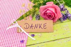 Kortet med det tyska ordet, Danke hjälpmedel tackar dig och den romantiska rosa färgrosblomman Royaltyfria Bilder