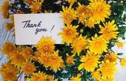 Kortet med handskriven text tackar dig på en bakgrund av blomman Arkivfoto